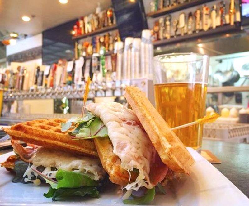 Iron Press' famous Monte Cristo sandwich: ham + jam, smothered with cheese and greens sandwiched between waffles.