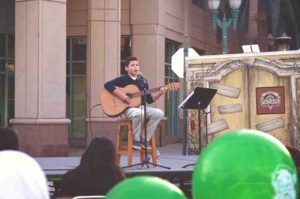 Kid singing and playing the guitar for audience in downtown Anaheim.